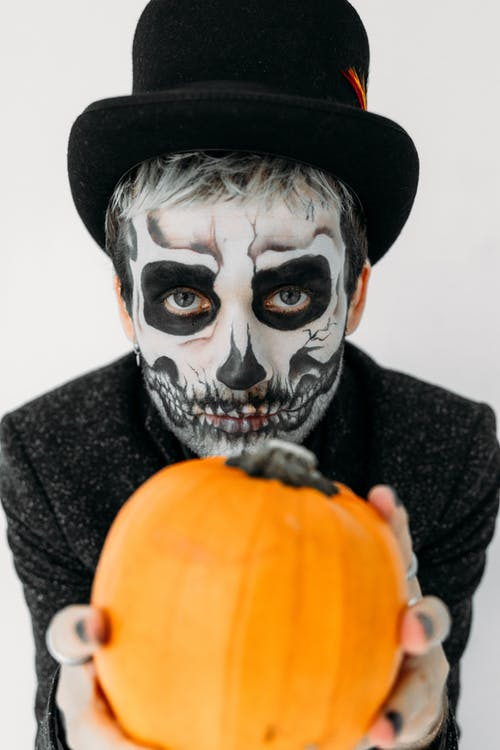 Person in Black and White Skull Face Paint Holding Pumpkin