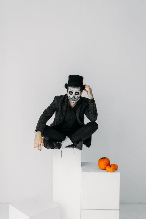 Man in Black Jacket and Black Hat Sitting on White Box