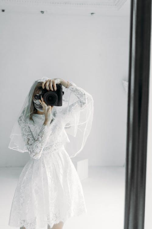 Femme En Robe De Mariée En Dentelle Florale Blanche Tenant Un Appareil Photo Reflex Numérique Noir