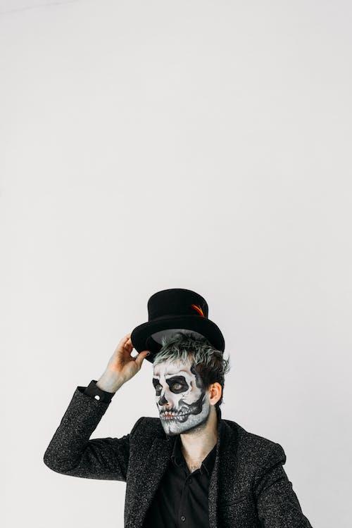 Homme Avec De La Peinture Pour Le Visage De Crâne Tenant Son Chapeau