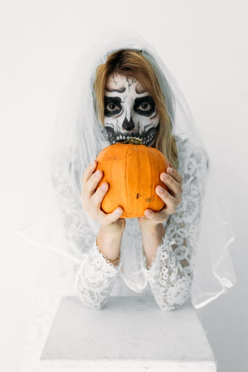 Woman in White Lace Dress Holding A Pumpkin