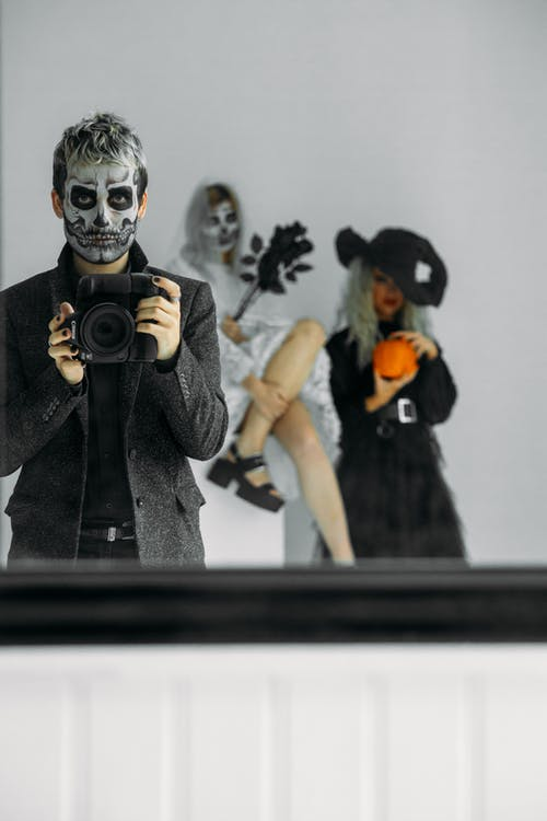 Reflections Of Three People With Different Halloween Costumes