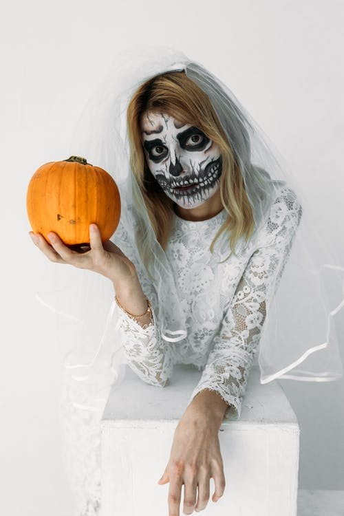 Woman in White Floral Lace Dress Holding A Pumpkin