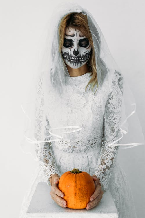 Woman in White Lace Dress Holding Pumpkin