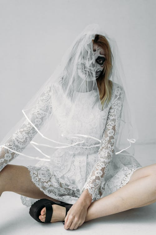 Woman in White Lace Dress And Skull Face Paint