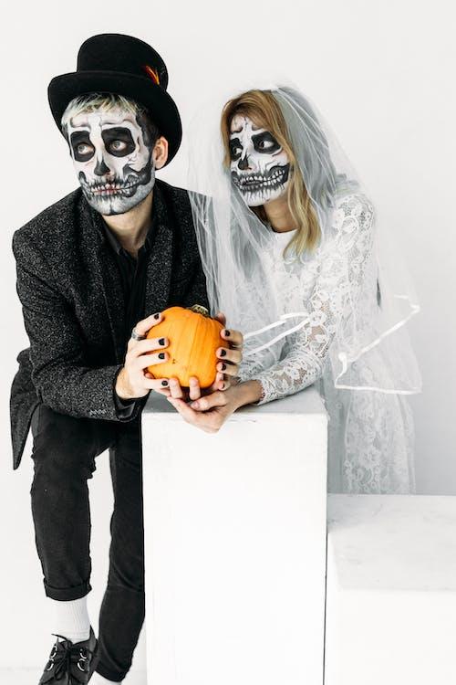 Homme Et Femme Avec Des Peintures De Visage De Crâne Tenant Une Citrouille