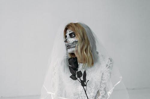 黒のバラと白いウェディングドレスの女性