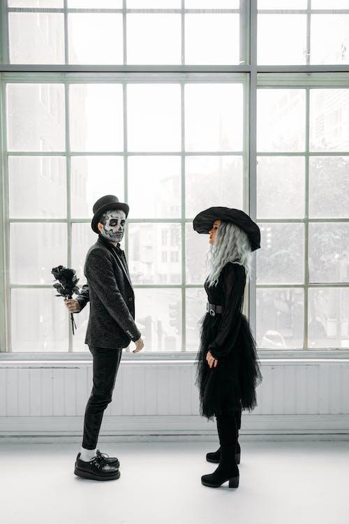 黒のドレスを着た女性の前に立っている黒いバラの束を保持している男
