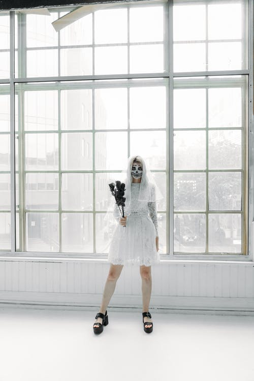 Woman in White Dress Standing Beside Window Holding A Bunsh Of Black Roses