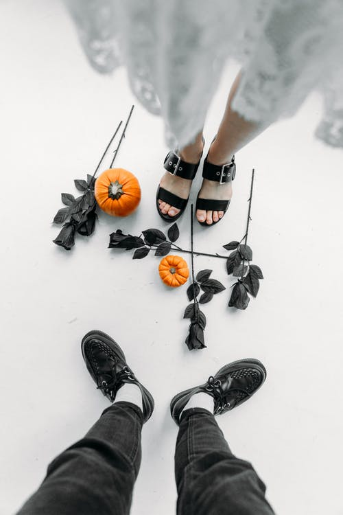 Man And Woman Standing Close To Each Other With Black Roses And Pumpkin On Floor