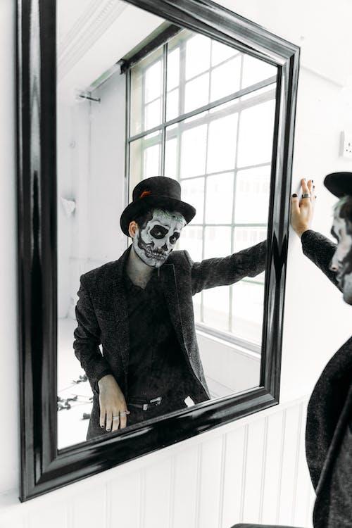 Man in Black Coat Standing Beside A Mirror
