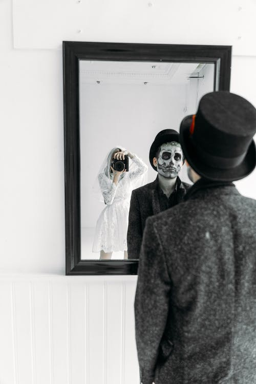 Reflections In The Mirror Of A Woman Holding A Camera And Man Standing Infront Of A Mirror