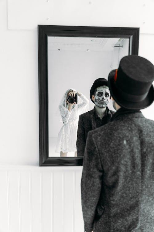 Reflexiones En El Espejo De Una Mujer Sosteniendo Una Cámara Y Un Hombre De Pie Delante De Un Espejo