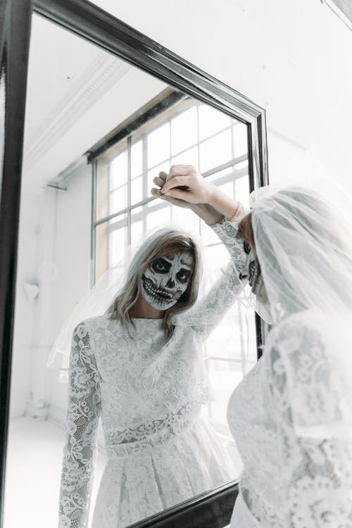 Reflection Of A Woman in White Floral Long Sleeve Dress With Scary Face Paint