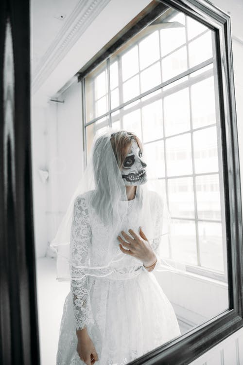 Woman in White Lace Dress Wearing Scary Mask Standing By The Window