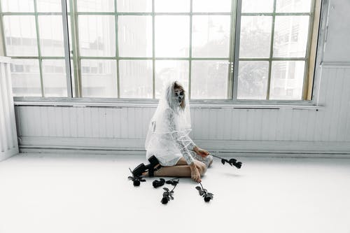 Woman in White Wedding Dress And Scary Face Paint Sitting on The Floor