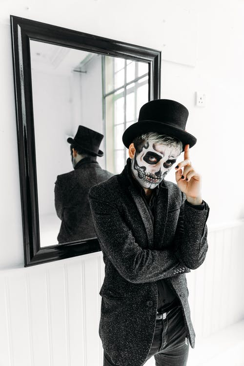 Man in Black Coat And Black Hat With Face Paint