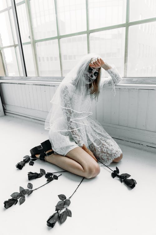 Woman in White Wedding Dress Sitting on The Floor