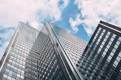 Modern skyscraper against cloudy blue sky