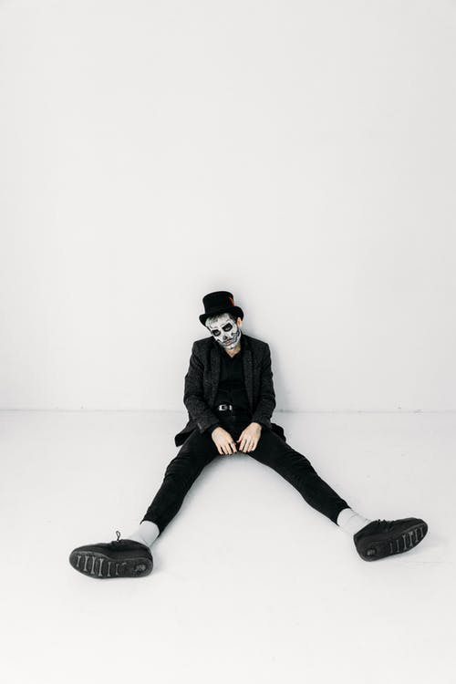 Man in Black Jacket and Black Pants Wearing Face Paint While Sitting on The Floor