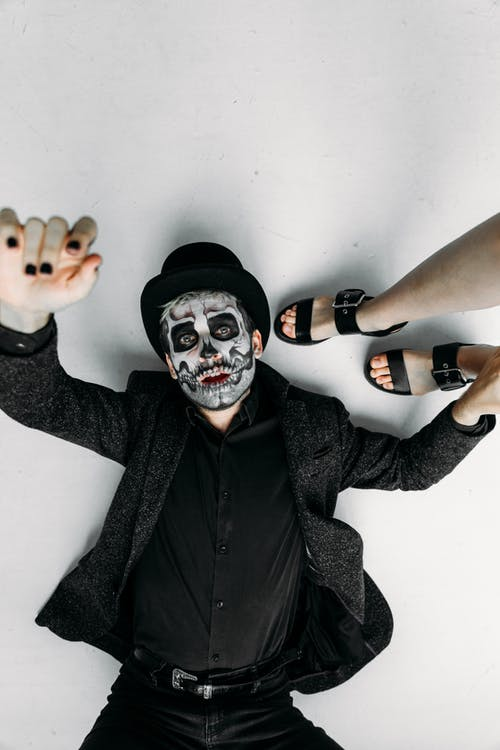Man in Black Coat With Face Paint In A Lying Position