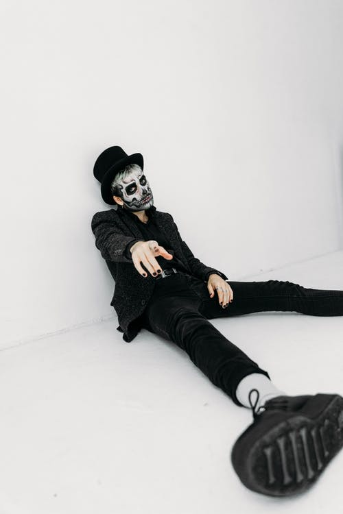 Man With Skull Face Paint Sitting On The Floor