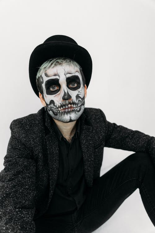 Man In Black With Face Paint Of A Skull
