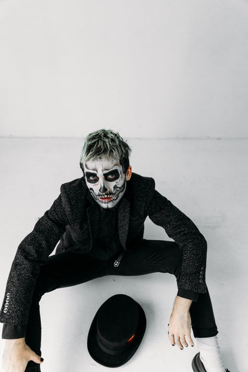 Man in Black With Scary Face Paint Sitting on Floor