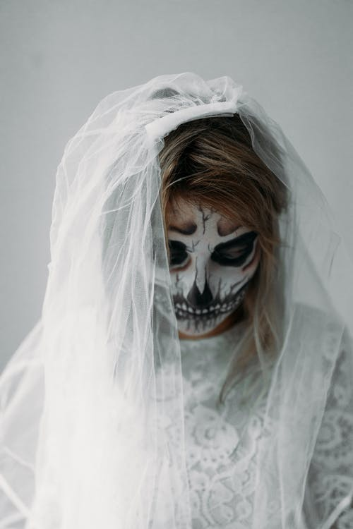 Person in White Lace Dress With Face Paint