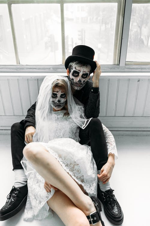 Woman in White Lace Wedding Dress and Man in Black Suit With Face Paints