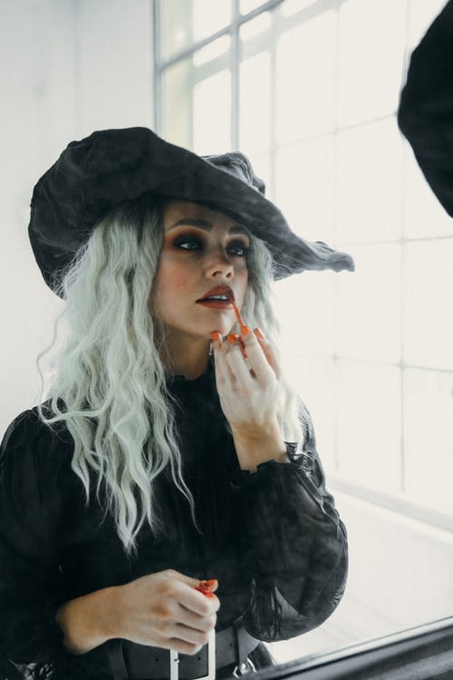 Woman in Black Witch Costume Applying Lip Gloss