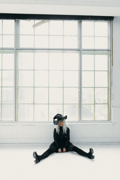 Woman In Black Witch Costume Sitting On The Floor