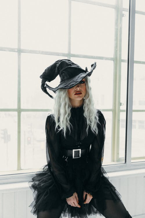 Woman in Black Witch Hat and Dress Sitting by the Windows