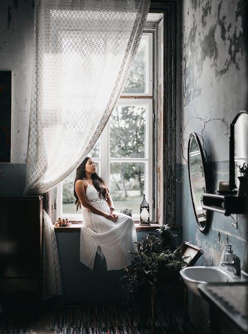 Charming woman resting on windowsill in shabby bathroom