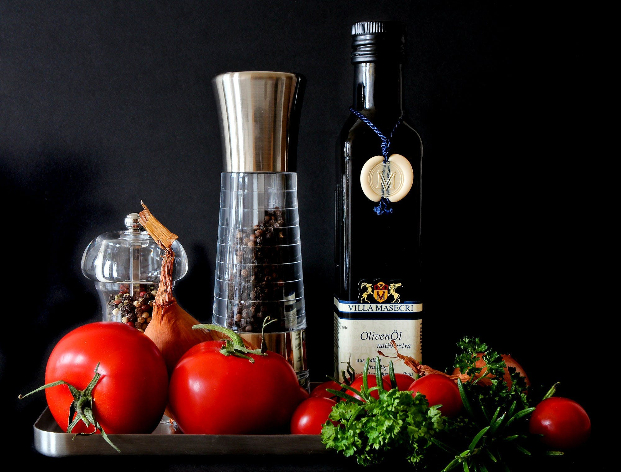 Tomatoes Beside Shakers and Olive Oil Bottle