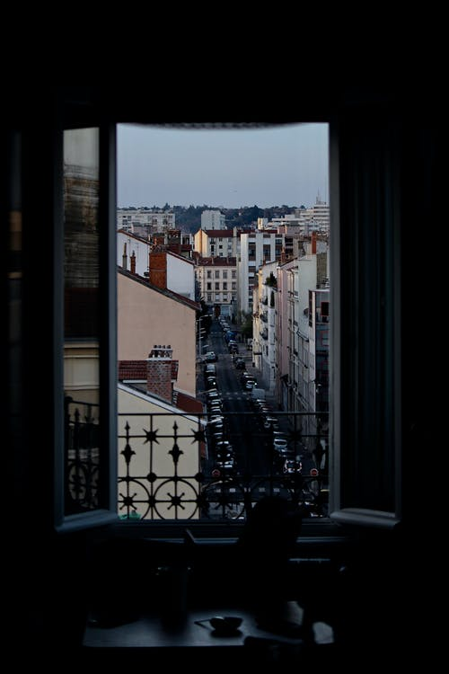 Dark room with window with metal fence overlooking cityscape with road and colorful buildings against cloudless sky in city street
