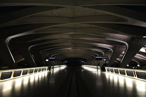 Perspective view of modern dark empty train station with illuminated sides of walkway and futuristic ceiling in night time inside