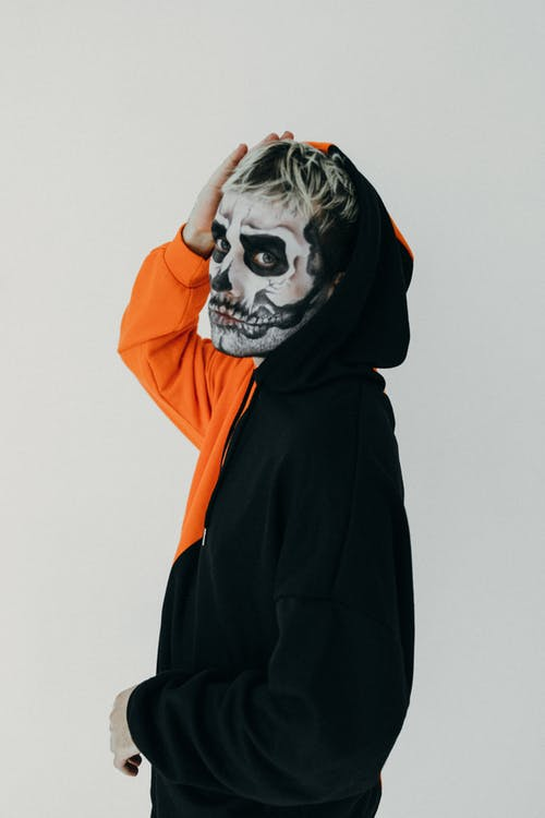Person in Black and Orange Hoodie With Halloween Face Art