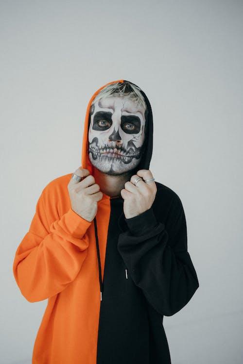 Mann In Orange Und Schwarz Hoodie Mit Halloween Face Art