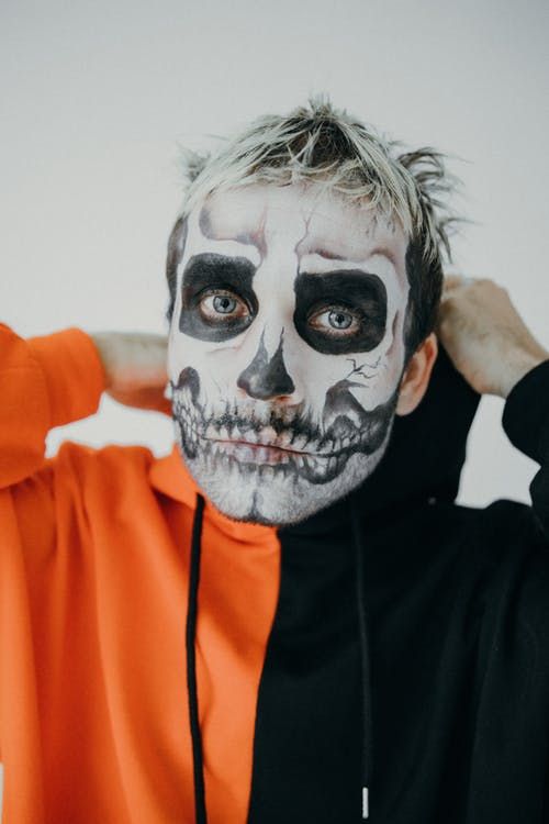 Man in Orange and Black Hoodie With Halloween Face Art