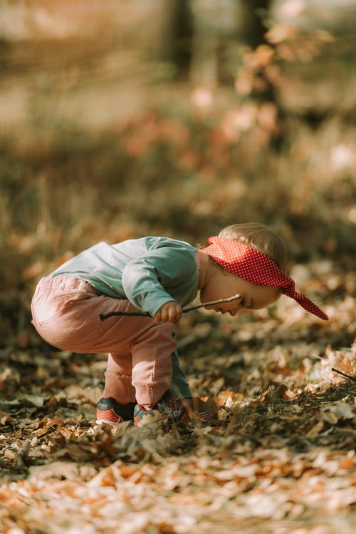 Little girl playing in autumn forest