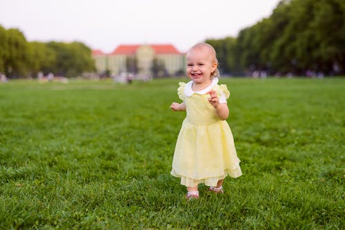 Happy little girl walking on lawn