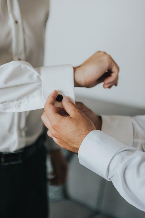 Crop man fasten cufflinks on shirt of groom