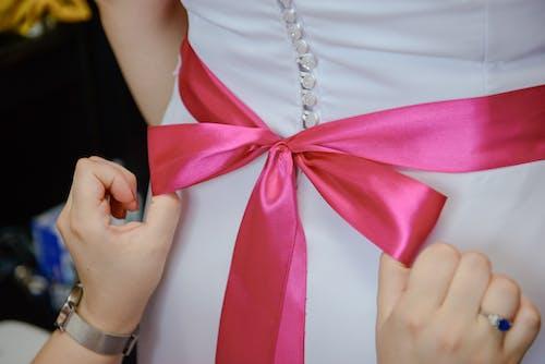 Crop bridesmaid tying bow on dress of bride