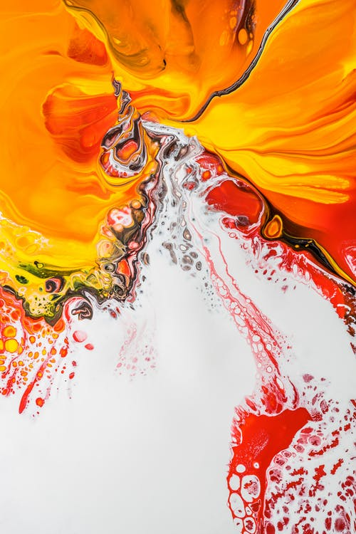 Abstract background painting with red splatters on white fluid acrylic paint and orange stains creating original patterns on creative drawing