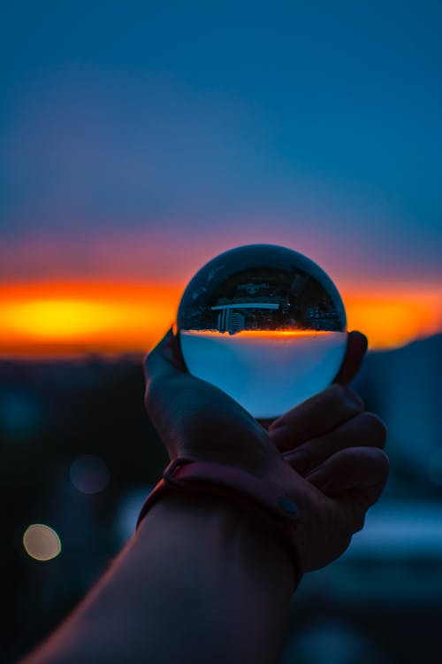 Unrecognizable person with sunset sky reflecting upside down in glass ball in sundown time in city on blurred background outside