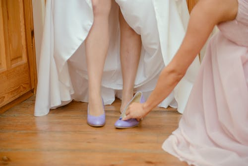 Unrecognizable bridesmaid helping bride putting on shoes on floor