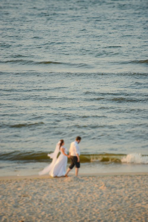 Side view of unrecognizable groom and bride in white dress holding hands and walking on sandy beach near waving ocean after wedding ceremony at sunset
