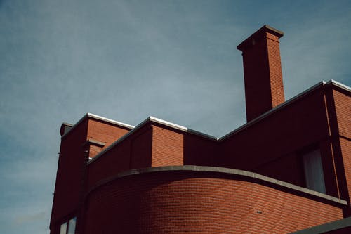 From below of contemporary brick residential construction with glass windows and geometric design