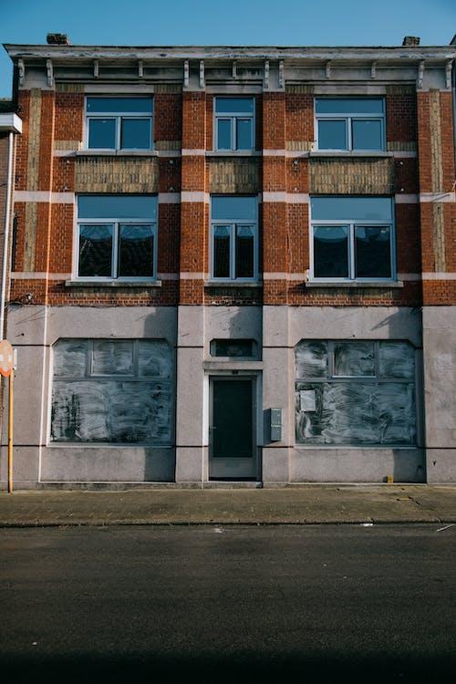 Old shabby building on asphalt road
